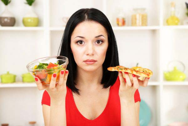 A Young Woman holding a bowl of salad and a pizza